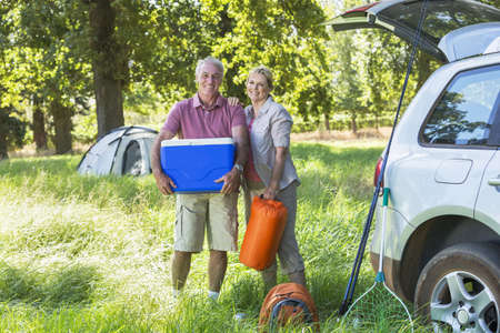 ice chest: Senior Couple Unpacking Car For Camping Trip In Countryside LANG_EVOIMAGES