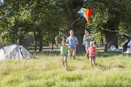 woman flying: Family Flying Kite On Camping Holiday In Countryside