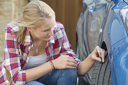 tyre tread: Woman Checking Tread Depth On Car Tyre
