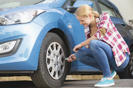 Woman Checking Tyre Pressure On Car Reklamní fotografie - 28618535