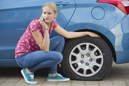 flat tyre: Woman With Flat Tyre On Car Phoning For Assistance