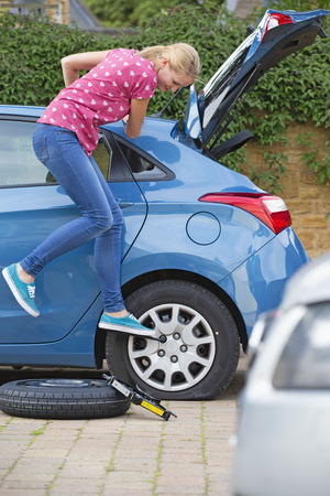 flat tyre: Woman Changing Flat Tyre On Car