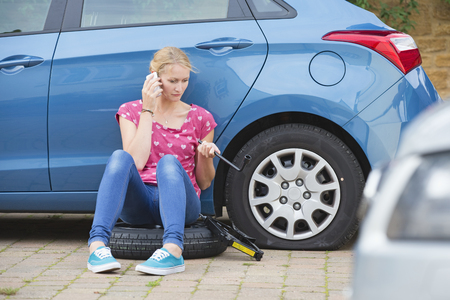 Woman With Flat Tyre On Car Phoning For Assistance