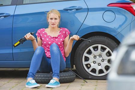 좌절 된 여자 플랫 타이어에서 자동차를 변경하려고 스톡 콘텐츠