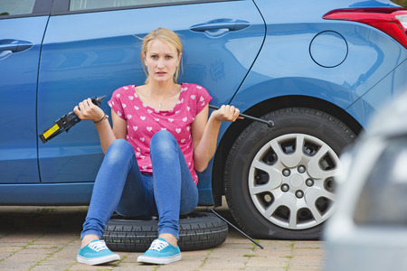 flat tyre: Frustrated Woman Trying To Change Flat Tyre On Car