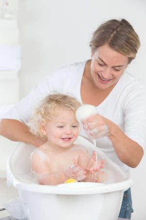 bathe: Smiling mother bathing happy baby in bathtub