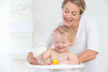 woman bath: Smiling mother bathing happy baby in bathtub