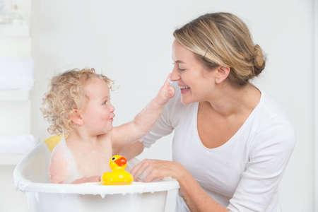 limpieza: Ba�o sonriente de la madre al beb� feliz en la ba�era LANG_EVOIMAGES