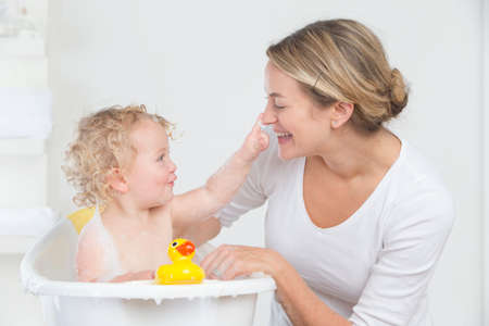 woman in bath: Smiling mother bathing happy baby in bathtub