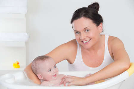 Smiling mother bathing happy baby in bathtub