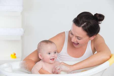 personas banandose: Ba�o sonriente de la madre al beb� feliz en la ba�era LANG_EVOIMAGES