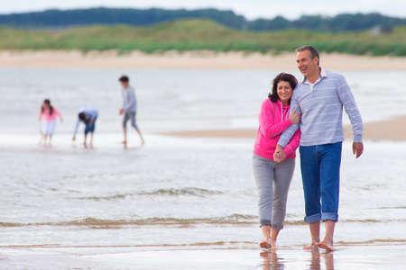 Grandparents walking as grandchildren play on beach