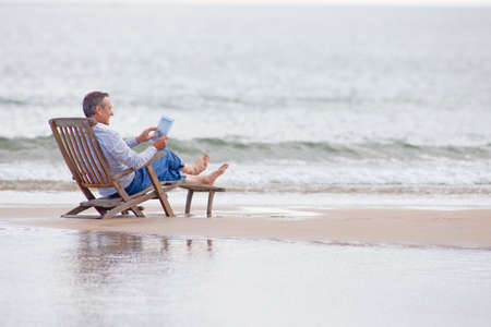 senior reading: Older man using digital tablet in deck chair on beach LANG_EVOIMAGES