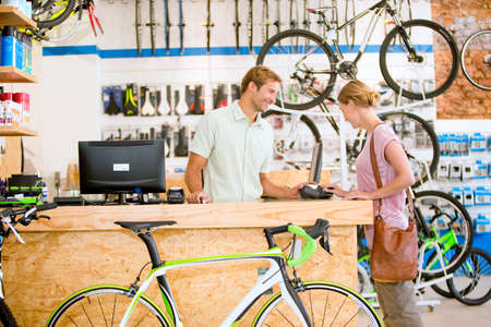 rental: Store manager assisting customer in bicycle shop LANG_EVOIMAGES