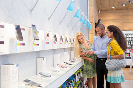 electronic store: Store manager assisting two female customers in phone store