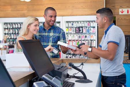 pagando: Pareja hacer una compra de asistente de la tienda en tienda de telefon�a LANG_EVOIMAGES