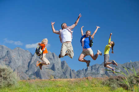 Family jumping in the air on a mountain hiking trail