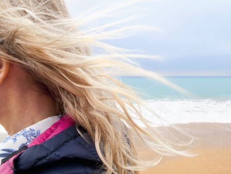 breeze: Blond hair blowing in breeze on beach LANG_EVOIMAGES