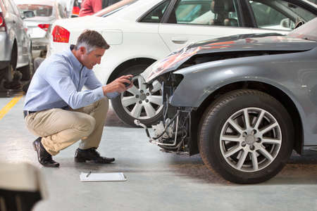 total loss: Insurance assessor inspecting damaged vehicle