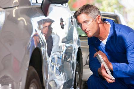 pileup: Mechanic inspecting damaged vehicle LANG_EVOIMAGES
