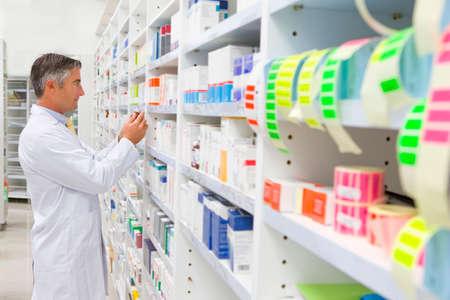 Pharmacist reading pack of medicine from pharmacy shelf