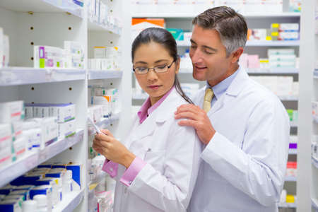 Pharmacist placing hand on colleagues shoulder in pharmacy LANG_EVOIMAGES