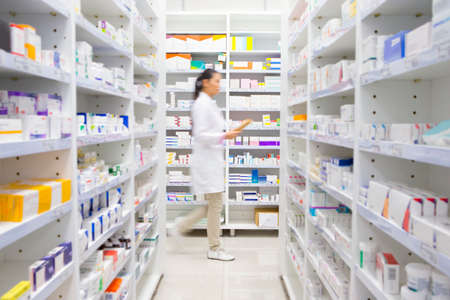 Pharmacist walking through pharmacy Stock Photo