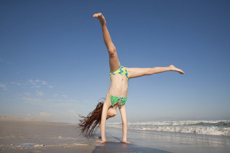 Redheaded Girl doing handstand on sunny beach