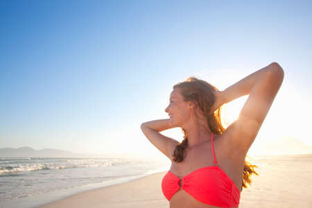 arms behind head: Smiling woman, with arms raised behind head, on sunny beach LANG_EVOIMAGES