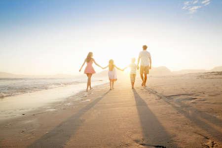 mujer mirando el horizonte: Familia feliz caminando en la distancia, de la mano, en la playa asoleada
