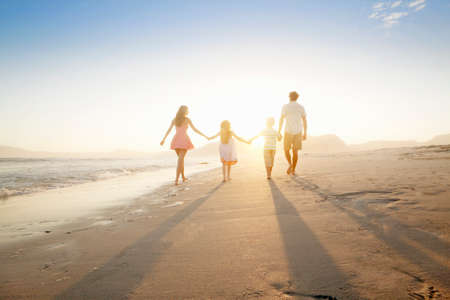 active family: Happy family walking into distance, holding hands, on sunny beach