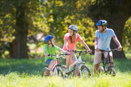 mountain biking: Family, mountain biking, in treelined field LANG_EVOIMAGES