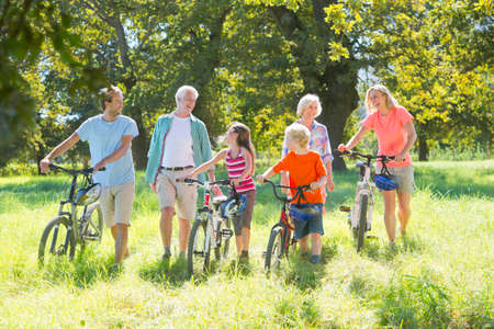 mountain bicycling: Multi generation family, pushing mountain bikes, in treelined field