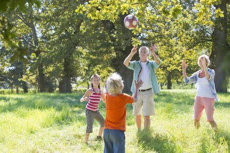 multi generation: Multi generation family, playing catch, in treelined field