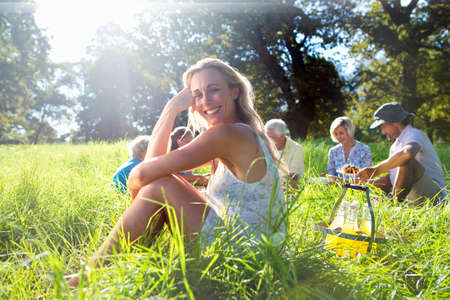 multi generation: Portrait of smiling woman and multi generation having picnic in treelined field LANG_EVOIMAGES