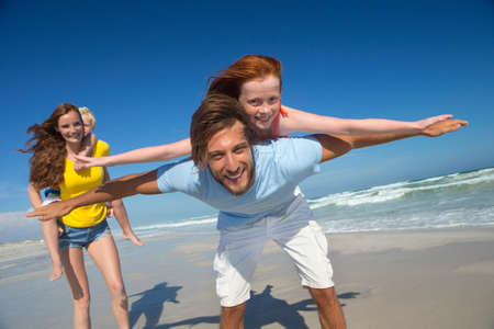 liberated: Mother and father, giving two children piggy back, on sunny beach