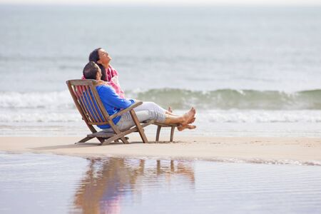 unwinding: Couple relaxing together on deck chair in beach