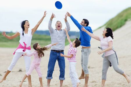 multigeneration: Multi-generation family throwing plastic disc on beach