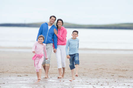 getting away from it all: Family walking together on beach LANG_EVOIMAGES
