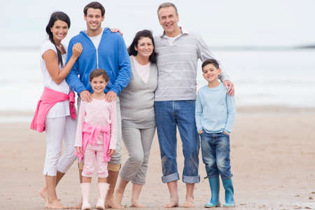 getting away from it all: Multi-generation family smiling together on beach