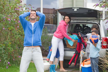 stressed people: Frustrated father shouting as family packs car for vacation
