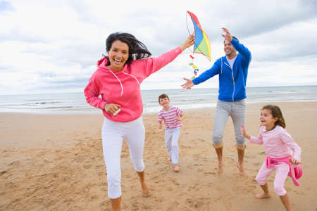 flying woman: Family flying kite on beach
