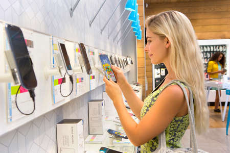 electronics store: Young woman browsing in phone store