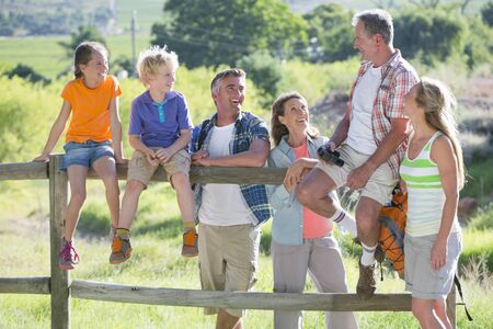 Multi generation family resting on a fence in a rural setting Stock Photo