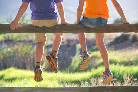 dangling: Children sat on fence with feet dangling