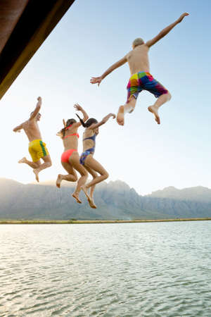 limitless: Family, in swimwear, jumping into a lake from a jetty