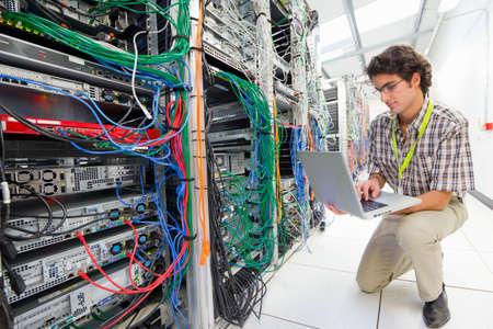 Technician, kneeling, working on laptop computer in Server room of data center Stock Photo