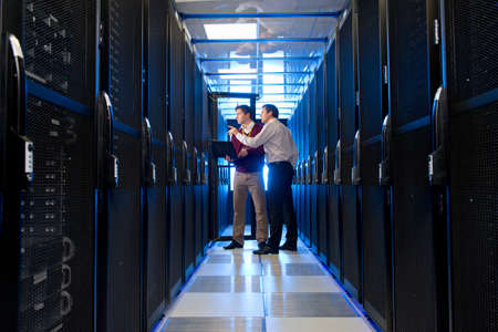 Manager and technician, with laptop, talking in aisle of server room Stock Photo