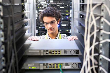 Technician replacing server in server cabinet Stock Photo