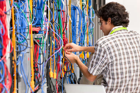 Technician, checking cables in Server room of data center Stock Photo